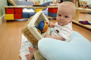 Sitting up infant with treasure basket